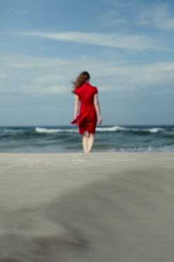 Magdalena Russocka woman in red dress walking on beach