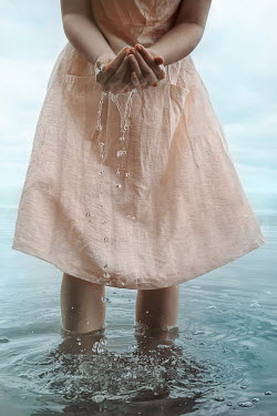 Natasza Fiedotjew woman in peachy dress standing in water scooping up water in cupped hands