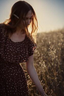 Natasza Fiedotjew redhead girl standing in oat field at sunset