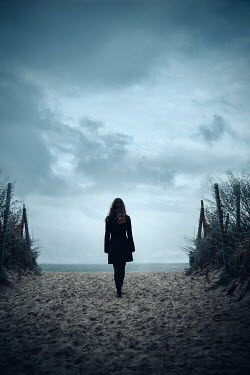Natasza Fiedotjew woman in black jacket entering seashore