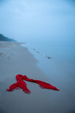 Natasza Fiedotjew red fringy shawl dropped on beach by sea