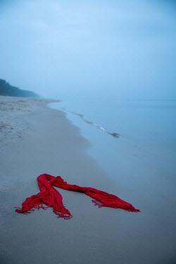 Natasza Fiedotjew red fringy shawl dropped on beach by sea