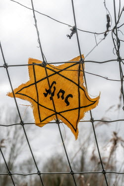 CollaborationJS YELLOW STAR OF DAVID BADGE ON WIRE FENCE