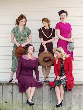Elisabeth Ansley GROUP OF RETRO WOMEN SITTING AND STANDING ON VERANDA