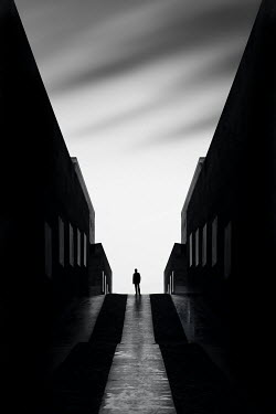 Evelina Kremsdorf SILHOUETTED MAN STANDING BY BUILDINGS IN SHADOW
