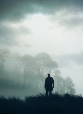 Mark Owen SILHOUETTED MAN IN COAT STANDING IN COUNTRYSIDE