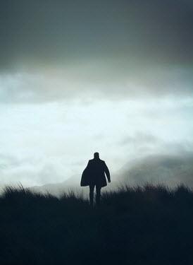 Mark Owen SILHOUETTED MAN IN COAT WALKING IN COUNTRYSIDE