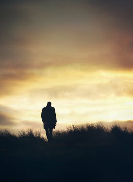 Mark Owen SILHOUETTED MAN IN COAT WALKING IN FIELD