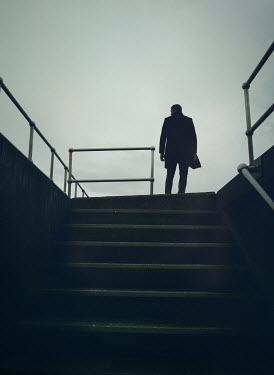 Mark Owen SILHOUETTED MAN IN COAT STANDING ON STEPS