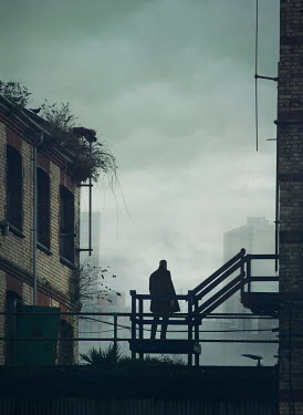 Mark Owen SILHOUETTED MAN IN COAT STANDING BY URBAN BUILDINGS