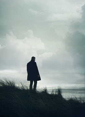 Mark Owen MAN IN COAT STANDING ON DUNES WATCHING SEA