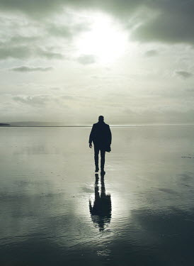 Mark Owen SILHOUETTED MAN WALKING ON WET BEACH