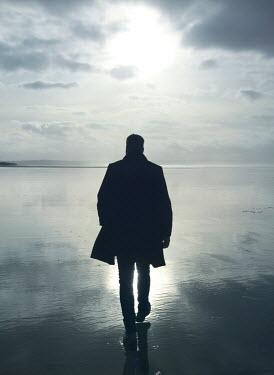 Mark Owen SILHOUETTED MAN WALKING ON WET BEACH
