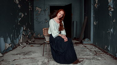 Georgy Chernyadyev WOMAN WITH RED HAIR SITTING IN DERELICT BUILDING