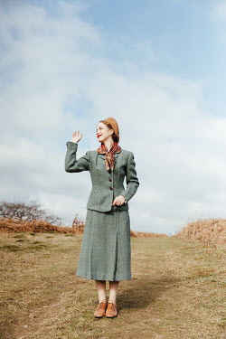 Matilda Delves RETRO WOMAN SMILING AND WAVING IN COUNTRYSIDE