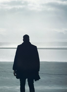 Mark Owen SILHOUETTED MAN IN COAT ON SANDY BEACH