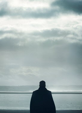 Mark Owen SILHOUETTED MAN IN COAT WATCHING BEACH