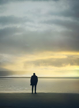 Mark Owen SILHOUETTED MAN STANDING ON BEACH AT SUNSET