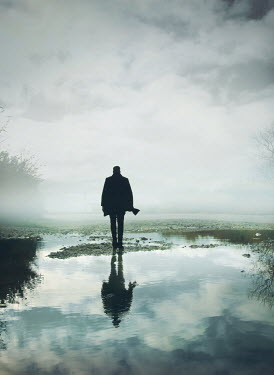 Mark Owen SILHOUETTED MAN WALKING IN FLOODED FIELD