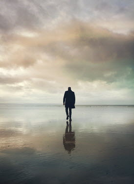 Mark Owen SILHOUETTED IN COAT MAN WALKING ON BEACH