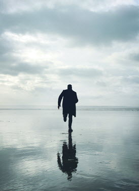 Mark Owen SILHOUETTED MAN IN COAT RUNNING ON BEACH