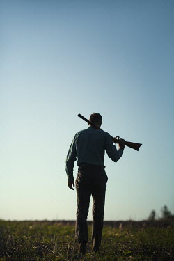 Magdalena Russocka man holding rifle walking in field