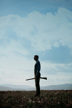 Magdalena Russocka man holding rifle standing in field