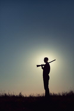 Magdalena Russocka man holding rifle standing in field at sunset