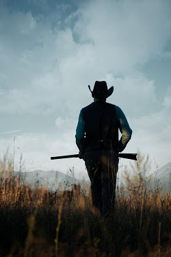 Magdalena Russocka cowboy man holding rifle walking in field