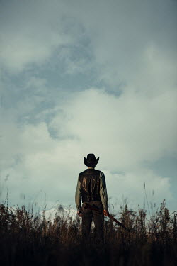 Magdalena Russocka cowboy man holding rifle standing in field
