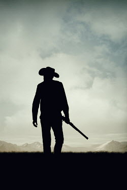 Magdalena Russocka silhouette of cowboy man holding rifle walking in field