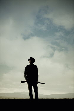 Magdalena Russocka silhouette ofcowboy man holding rifle standing in field