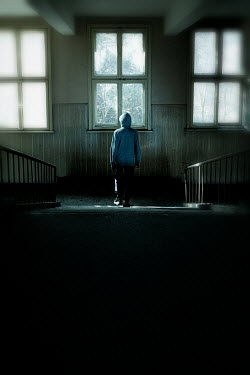 Des Panteva YOUNG BOY IN HOODIE STANDING IN SHABBY BUILDING
