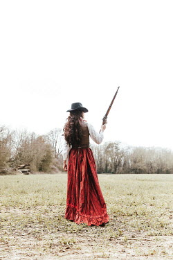 Matilda Delves HISTORICAL WOMAN STANDING WITH RIFLE IN COUNTRYSIDE
