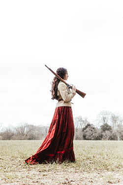 Matilda Delves HISTORICAL WOMAN STANDING WITH RIFLE OUTDOORS