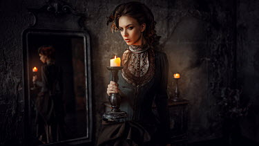 Georgy Chernyadyev WOMAN HOLDING CANDLE BY MIRROR IN DARK BUILDING