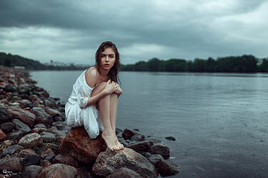 Georgy Chernyadyev BAREFOOT BRUNETTE WOMAN SITTING BY RIVER