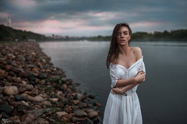 Georgy Chernyadyev BRUNETTE WOMAN STANDING BY RIVER AT DUSK