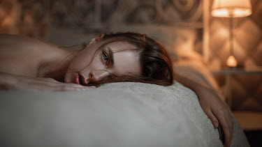 Georgy Chernyadyev BRUNETTE WOMAN LYING ON BED WITH LAMPLIGHT
