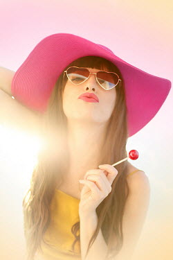 ILINA SIMEONOVA WOMAN IN HAT HOLDING LOLLIPOP OUTDOORS
