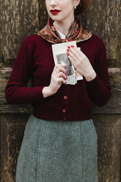 Matilda Delves WOMAN HOLDING PHOTOS BY DOOR OUTSIDE
