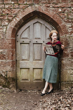 Matilda Delves RETRO WOMAN READING MAGAZINE OUTSIDE DOORWAY