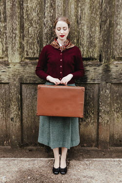 Matilda Delves RETRO WOMAN HOLDING SUITCASE OUTSIDE LARGE DOORWAY