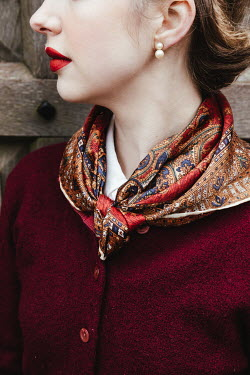 Matilda Delves RETRO WOMAN WITH PEARL EARRINGS AND SCARF OUTDOORS