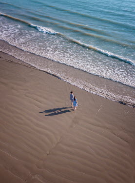 Mary Wethey TWO WOMAN HOLDING HANDS ON BEACH FROM ABOVE