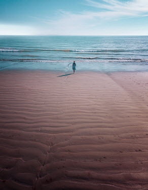 Mary Wethey WOMAN IN DISTANCE WALKING ON SANDY BEACH