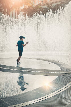 Evelina Kremsdorf LITTLE BOY IN CAP PLAYING IN FOUNTAIN