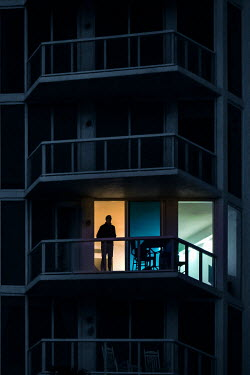 Evelina Kremsdorf SILHOUETTED MAN ON APARTMENT BALCONY AT NIGHT