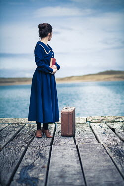 Marie Carr WOMAN WITH BOOK AND SUITCASE ON JETTY BY SEA