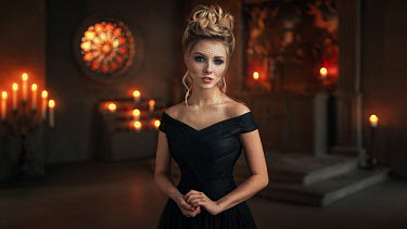 Georgy Chernyadyev BLONDE WOMAN IN BLACK INSIDE CHURCH WITH CANDLES